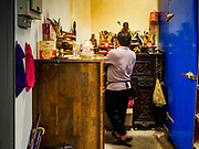 24 AUGUST 2018 - GEORGE TOWN, PENANG, MALAYSIA: An ethnic Chinese shop keeper prays in a small shrine in Chowrasta Market in central George Town. Chowrasta Market was originally built in 1890 and is the older of two traditional markets in George Town. The original building was torn down and replaced with a modern building in 1961 and has been renovated several times since.     PHOTO BY JACK KURTZ