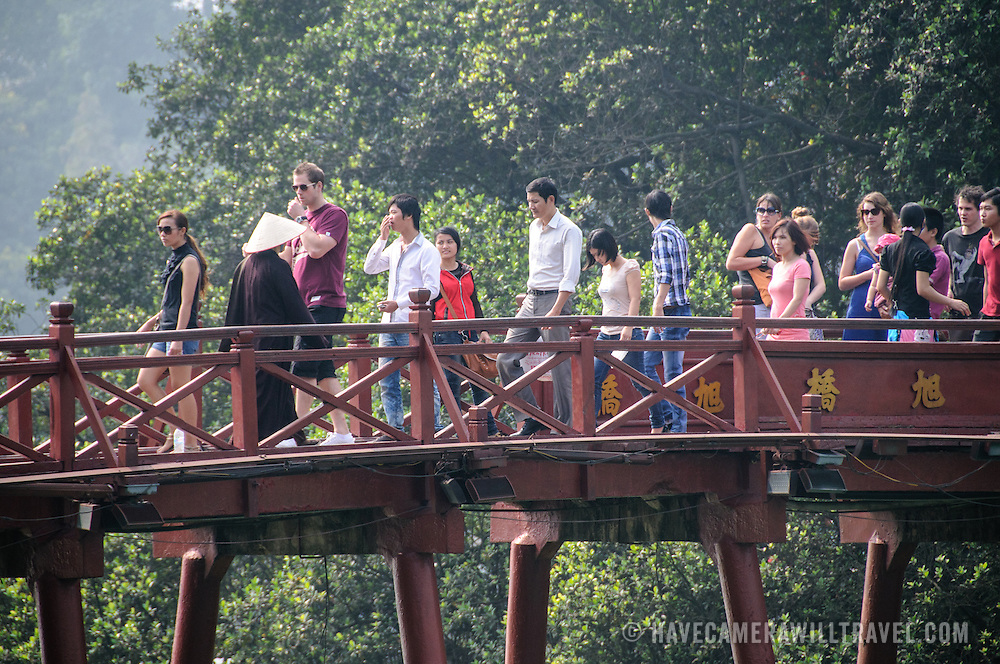 Tourists walk across The Huc Bridge (Morning Sunlight Bridge). The red-painted, wooden bridge joins the northern shore of the lake with Jade Island and the Temple of the Jade Mountain (Ngoc Son Temple).