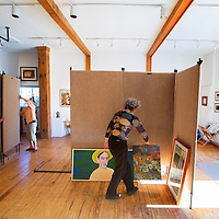 100313       Brian Leddy<br /> Rachel Schali, Pam Davis and Be Sargent hang artwork at the Old School Gallery in El Morro Thursday. Members of the Gallup Arts council and the El Morro Arts Council are doing a collaborative show for the month of October.