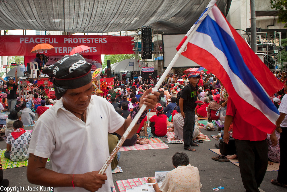 """May 12 - BANGKOK, THAILAND: A Thai Red Shirt carries the Thai flag through the crowd in front of the Red Shirts' main stage Wednesday. The Thai government said Wednesday that time has run out for """"Red Shirt"""" protesters in Ratchaprasong and Sala Daeng intersections in Bangkok and that a crackdown could come at any time. As news of the anticipated crackdown spread, Red Shirt protesters continued with an almost festive mood at their main stage but many of the sleeping areas around the protest site appeared to be empty. No official estimates on crowd size are available.  Photo by Jack Kurtz"""