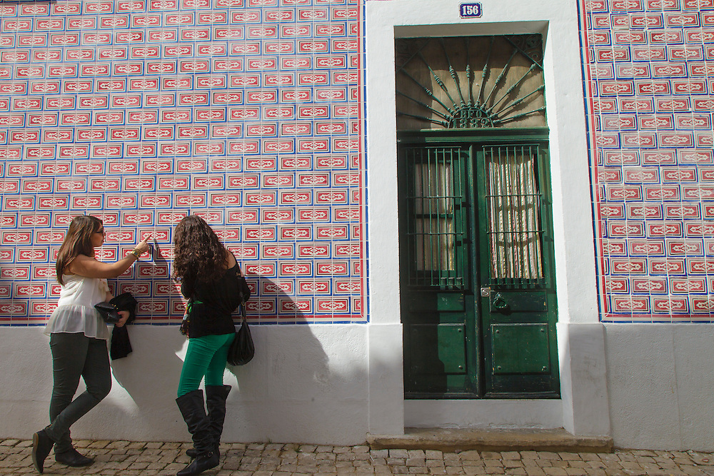 Two ladies looking at ceramic tiles facades in Madragoa district in Lisbon.
