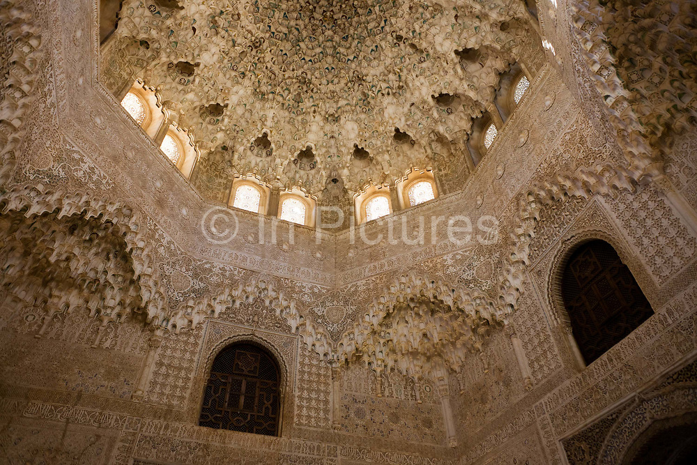 Ornate domed architecture in the Sala de dos Hermanas (Hall of the Two Sisters) in Alhambra Palace. The hall was built by order of Mohammed V. It is square, has interlacing ceilings and bedchambers connected with the Emperor's Chambers (Habitaciones de Carlos V). Arabesque arches and fine carvings adorn this finely-detailed Moorish architecture - well preserved by Spanish authorities. Alhambra (in Arabic, Al-Ḥamra) is a palace and fortress complex constructed during the mid 14th century by the Moorish rulers of the Emirate of Granada in Al-Andalus, occupying the top of the hill of the Assabica on the southeastern border of the city of Granada in the Autonomous Community of Andalusia. The Alhambra's Moorish palaces were built for the last Muslim Emirs in Spain and its court, of the Nasrid dynasty.