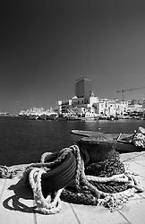 Groviglio di funi e cime lungo il molo del porto di Gallipoli (LE). lo pneumatico viene usato come respingente per evitare che le barche urtino la banchina del porto.
