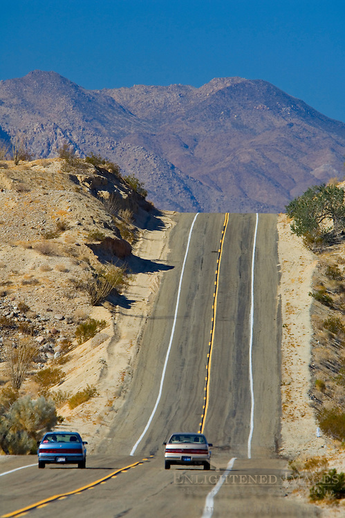Car passing on two lane desert road approaching a hill, Anza Borrego Desert State Park, San Diego County, California