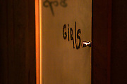 The door to the ladies' toilet the restaurant CRU in Montevideo, supposedly one of the better and trendier restaurants in the city. Glass door with girls painted in what looks like hand paint and a small metal door knob. Montevideo, Uruguay, South America