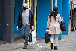 © Licensed to London News Pictures. 25/10/2020. Manchester, UK. A man wearing a face mask carries his shopping bags down Market Street, Manchester. Shoppers in Manchester aren't deterred by new tier 3 restriction or potential tier 4 restrictions, which could see retail and restaurants closed. Photo credit: Kerry Elsworth/LNP