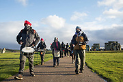 Samba drummers join over one hundred people, including local residents, climate and land justice activists and pagans, at a Mass Trespass at Stonehenge on 5th December 2020 in Salisbury, United Kingdom. The trespass was organised in protest against the approval by Transport Secretary Grant Shapps of a £1.7bn project for a two-mile tunnel beneath the World Heritage Site and a further eight miles of dual carriageway for the A303, as well as the government's £27bn Road Investment Strategy 2 (RIS2).