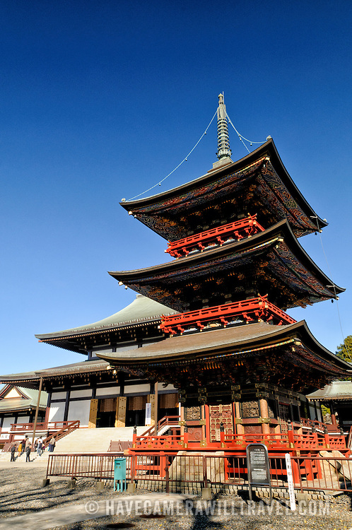The Three Storied Pagoda, standing 25 meters tall, was originally built in 1712. It is ornately decorated with brightly painted rafters, carved dragons, and sculptures of 16 RAKAN or Buddha's disciples how attained Nirvana. On the first floor's inner sanctum is GOCHI-NYORAI (Five Tathagas) who is believed to be endowed with the five wisdoms of Buddha. In the background is the front of the Great Main Hall. The Narita-san temple, also known as Shinsho-Ji (New Victory Temple), is Shingon Buddhist temple complex, was first established 940 in the Japanese city of Narita, east of Tokyo.