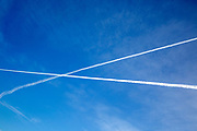 Two aeroplane contrails crossing each other in deep blue sky