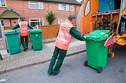 Binmen collecting refuse from neighbourhood wheelie bins and loading them into dust cart,