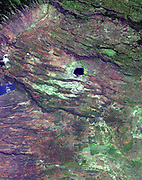 Places where the earth's crust has formed deep fissures and the plates have begun to move apart develop rift structures in which elongate blocks have subsided relative to the blocks on either side. The East African Rift is a world-famous example of such rifting. It is characterized by 1) topographic deep valleys in the rift zone, 2) sheer escarpments along the faulted walls of the rift zone, 3) a chain of lakes within the rift, most of the lakes highly saline due to evaporation in the hot temperatures characteristic of climates near the equator, 4) voluminous amounts of volcanic rocks that have flowed from faults along the sides of the rift, and 5) volcanic cones where magma flow was most intense. This example in Kenya displays most of these features near Lake Begoria.
