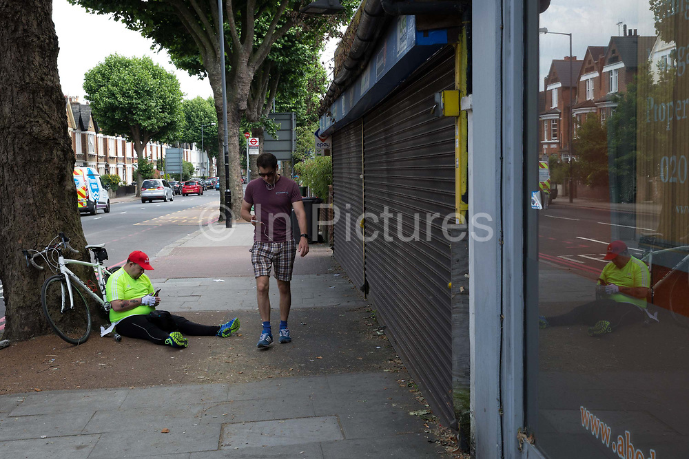 An male cyclist sitting on the pavement using his mobile phone on 17th June 2017 in London, United Kingdom.  From the series Our Small World, an observation of our mobile phone obsessions