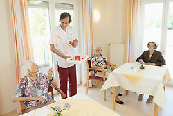 Caregiver giving medicine to senior woman at rest home, Bavaria, Germany