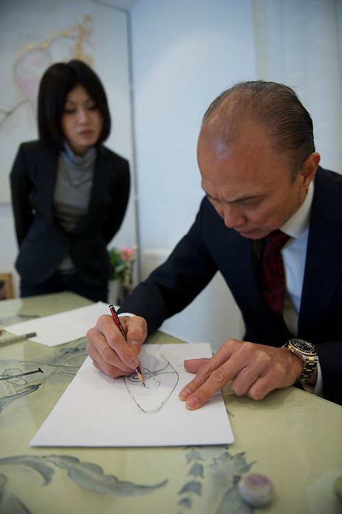 Fashion designer Jimmy Choo sketches in his store on Cannaught Street, London, March 22, 2010