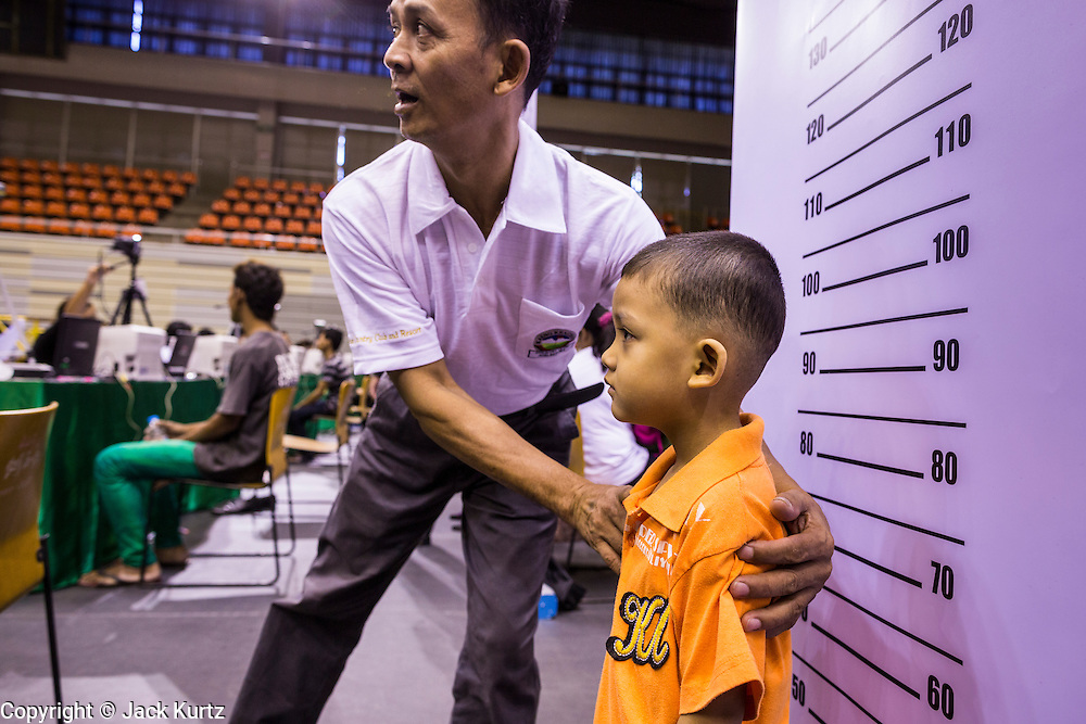 "17 JULY 2014 - BANGKOK, THAILAND:  An undocumented Cambodian man helps his son pose for a ""mug shot"" for his temporary ID card at the ""one stop service center"" in the Bangkok Youth Center in central Bangkok. Thai immigration officials have opened several temporary ""one stop service centers"" in Bangkok to register undocumented immigrants and issue them temporary ID cards and work permits. The temporary centers will be open until August 14.   PHOTO BY JACK KURTZ"