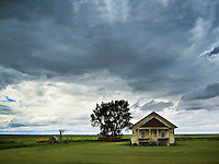 Abandoned farmhouse sits on a flat horizon, menacing storm clouds overhead, Saskatchewan