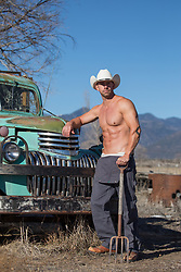 shirtless muscular working cowboy by a truck
