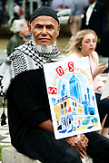 East End, London July 5th 2014. Rally and march against proposed cuts to National Health Service doctors' surgeries , specifically MPIG (Minimum Practice Income Guarantee payments) brought in to ensure practices in deprived areas had enough money to deliver high quality General Practice services. A Muslim man from the Bangladeshi community holds a placard and listens to speeches.