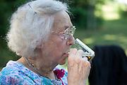 Polish great grandmother enjoying a cup of beer at family picnic. Zawady Central Poland