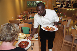 Chef serving plates of food to customer in Caribbean restaurant,