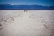 Tourists stand on the dried salt deposits at Badwater Basin, the lowest point on earth in Death Valley National Park, Nevada, USA.