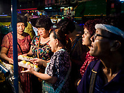 27 FEBRUARY 2019 - BANGKOK, THAILAND: Women look at durian, a pungent tropical fruit, at a street stall in Bangkok. Bangkok, a city of about 14 million, is famous for its raucous nightlife. But Bangkok's real nightlife is seen in its markets and street stalls, many of which are open through the night.         PHOTO BY JACK KURTZ