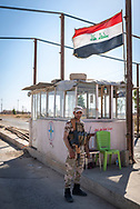 A Christian NPU soldier stands at a highway checkpoint at the entrance to the predominately Christian town of Qaraqosh, Iraq. The NPU (Nineveh Plain Protection Units) is a military organization formed late in 2014, mostly by Assyrian Christians, to defend themselves against ISIS. (May 20, 2017)