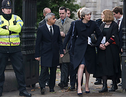 © Licensed to London News Pictures. 14/12/2017. London, UK. Mayor of London SADIQ KHAN and British prime minister THERESA MAY leave St Paul's Cathedral in London following the Grenfell Tower National Memorial Service mark the six month anniversary of the Grenfell Tower fire. The service is attended by survivors of the fire and relatives of those who lost their lives in the fire, as well as members of the emergency services and members of the Royal family.  Over 70 people were killed when a huge fire ripped though 24-storey Grenfell Tower block in west London in June 2017.   Photo credit: Ben Cawthra/LNP