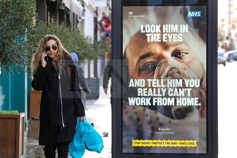 © Licensed to London News Pictures. 02/02/2021. London, UK. A woman wearing a protective face covering walks past the government's 'Look him in the eyes - And tell him you really can't work from home.' awareness publicity campaign poster in Haringey, north London. Door-to-door testing for the South Africa coronavirus variant will begin certain postcodes in the London boroughs of Merton, Haringey and Ealing to avoid the spread of the virus. Minister are telling members of the public in areas where South Africa variant has been found to 'think again' before leaving home. Photo credit: Dinendra Haria/LNP
