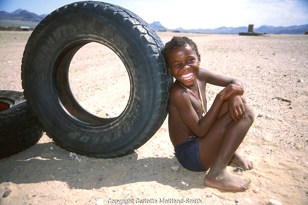 Young Herero boy  with old tyre in Purros village in Kaokoveld region north west Namibia Africa.The Herero's dress, consisting of several layers and, once married, a 'cow horn' head dress, derives from Victorian-era German missionaries who took exception to what they considered a lack of modesty among the local women..