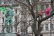 The statue of Field Marshal Jan Christiaan Smuts, the prominent South African and British Commonwealth statesman, military leader and philosopher and a climate change protester during the week-long action by climate change activists with Extinction Rebellions campaign to block road junctions and bridges around the capital, on 23rd April 2019, in London England.