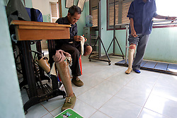 Khampieng 83 years old sitting down and Thongkat, 50 years old both amputees.<br /> Both have prosthetic legs provided by COPE and are able to walk very normally.   The COPE centre assists many people who have lost limbs due to UXO accidents. Pakse, Lao PDR.