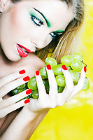 beautiful woman portrait with colorful make-up  and background holding grape