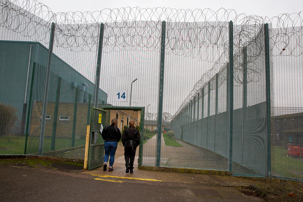 A woman escorted by a female prison officer is escorted through a gate to the medical centre inside HMP Downview, Surrey, United Kingdom. HMP Downview is a women's closed category prison for adult sentenced women and convicted and remand female young people located on the outskirts of Banstead in Surrey, England. (Picture credit: © Andy Aitchison)