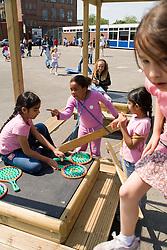 Children playing on climbing frame in school playground,