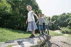 Girls balancing on tree trunk in playground, Munich, Bavaria, Germany