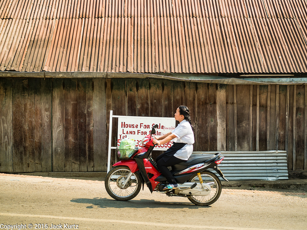 """13 MARCH 2016 - LUANG PRABANG, LAOS:  Lao people ride a motorcycle past a home for sale in Luang Prabang. The for sale sign being in English indicates who the property is being marketed to. Luang Prabang was named a UNESCO World Heritage Site in 1995. The move saved the city's colonial architecture but the explosion of mass tourism has taken a toll on the city's soul. According to one recent study, a small plot of land that sold for $8,000 three years ago now goes for $120,000. Many longtime residents are selling their homes and moving to small developments around the city. The old homes are then converted to guesthouses, restaurants and spas. The city is famous for the morning """"tak bat,"""" or monks' morning alms rounds. Every morning hundreds of Buddhist monks come out before dawn and walk in a silent procession through the city accepting alms from residents. Now, most of the people presenting alms to the monks are tourists, since so many Lao people have moved outside of the city center. About 50,000 people are thought to live in the Luang Prabang area, the city received more than 530,000 tourists in 2014.   PHOTO BY JACK KURTZ"""