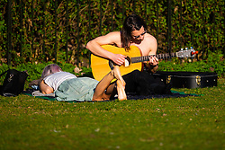A man play guitar as a woman sunbathes as crowds enjoy the unseasonably warm and sunny weather in Regents Park, London. London, February 26 2019.