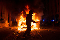 """© Licensed to London News Pictures;21/03/2021; Bristol, UK. A protestor is seen with a police baton in front of a police van which has been set on fire as police clash with protesters outside New Bridewell Police Station on Sunday evening during a """"Kill the Bill"""" protest against Police, Crime, Sentencing and Courts Bill takes place through the centre of Bristol during the Covid-19 coronavirus pandemic in England. The Bill proposes new restrictions on protests. Lockdown restrictions have been partly lifted to allow people to gather outdoors socially in households, bubbles, or to meet one person from another household, but the police say protests are not allowed under the current Covid regulations. Photo credit: Simon Chapman/LNP."""