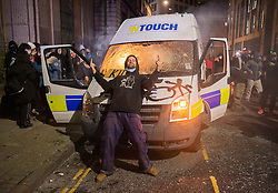 """© Licensed to London News Pictures;21/03/2021; Bristol, UK. Protestors attack a police van which is then set on fire as police clash with protesters outside New Bridewell Police Station on Sunday evening during a """"Kill the Bill"""" protest against Police, Crime, Sentencing and Courts Bill takes place through the centre of Bristol during the Covid-19 coronavirus pandemic in England. The Bill proposes new restrictions on protests. Lockdown restrictions have been partly lifted to allow people to gather outdoors socially in households, bubbles, or to meet one person from another household, but the police say protests are not allowed under the current Covid regulations. Photo credit: Simon Chapman/LNP."""