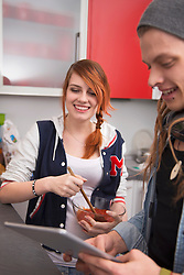 Young couple preparing food in kitchen, Munich, Bavaria, Germany