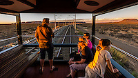 "Passengers sit out on the open air part of the observation car as the Rovos Rail train  ""Pride of Africa"" crosses the Great Karoo Desert on it's journey between Pretoria and Cape Town, South Africa."