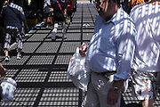 shadow of overhead metal grating projected on shopping people and road