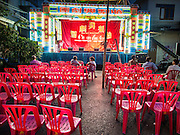 "18 AUGUST 2014 - BANGKOK, THAILAND:  The audience waits for the Lehigh Leng Kaitoung Opera troupe to come on stage during a performance at Chaomae Thapthim Shrine, a small Chinese shrine in a working class neighborhood of Bangkok. The performance was for Ghost Month. Chinese opera was once very popular in Thailand, where it is called ""Ngiew."" It is usually performed in the Teochew language. Millions of Chinese emigrated to Thailand (then Siam) in the 18th and 19th centuries and brought their culture with them. Recently the popularity of ngiew has faded as people turn to performances of opera on DVD or movies. There are still as many 30 Chinese opera troupes left in Bangkok and its environs. They are especially busy during Chinese New Year and Chinese holiday when they travel from Chinese temple to Chinese temple performing on stages they put up in streets near the temple, sometimes sleeping on hammocks they sling under their stage. Most of the Chinese operas from Bangkok travel to Malaysia for Ghost Month, leaving just a few to perform in Bangkok.       PHOTO BY JACK KURTZ"