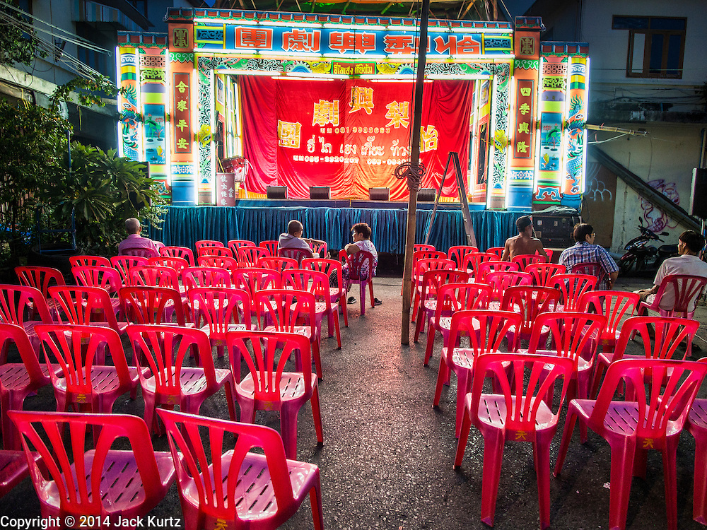 """18 AUGUST 2014 - BANGKOK, THAILAND:  The audience waits for the Lehigh Leng Kaitoung Opera troupe to come on stage during a performance at Chaomae Thapthim Shrine, a small Chinese shrine in a working class neighborhood of Bangkok. The performance was for Ghost Month. Chinese opera was once very popular in Thailand, where it is called """"Ngiew."""" It is usually performed in the Teochew language. Millions of Chinese emigrated to Thailand (then Siam) in the 18th and 19th centuries and brought their culture with them. Recently the popularity of ngiew has faded as people turn to performances of opera on DVD or movies. There are still as many 30 Chinese opera troupes left in Bangkok and its environs. They are especially busy during Chinese New Year and Chinese holiday when they travel from Chinese temple to Chinese temple performing on stages they put up in streets near the temple, sometimes sleeping on hammocks they sling under their stage. Most of the Chinese operas from Bangkok travel to Malaysia for Ghost Month, leaving just a few to perform in Bangkok.       PHOTO BY JACK KURTZ"""