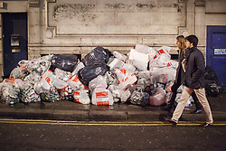 "© licensed to London News Pictures. London, UK 14/12/2013. ""Mad Friday"" revellers going past a pile of bin bags full of empty cans and bottles in Soho, London whilst enjoying the last Friday night out before Christmas, which is also the busiest night of the year for emergency services. Photo credit: Tolga Akmen/LNP"