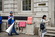 A women takes a selfie photograph as Anti Brexit campaigner Steve Bray protests outside the Cabinet Office in Whitehall as Ministers hold a Brexit Cabinet meeting on 16th August 2019 in London, United Kingdom.
