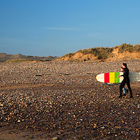 Europe, United Kingdom, Wales, Pembrokeshire. Surfers at Freshwater West Beach in Pembrokeshire.