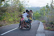 Nusa Penida, Indonesia - October 1, 2017: Shortly before sunset on the island of Nusa Penida near Bali, a man, woman, and two girls crowd together on a single motorbike for the ride home.