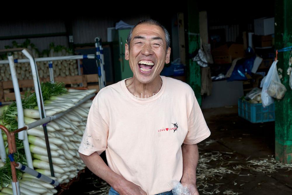 big smiling Japanese vegetable farmer harvesting daikon